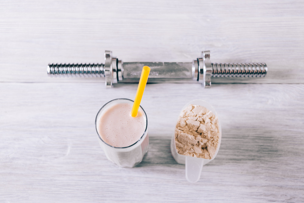 Protein cocktail in a glass, scoop and dumbbell on a white wooden table top view