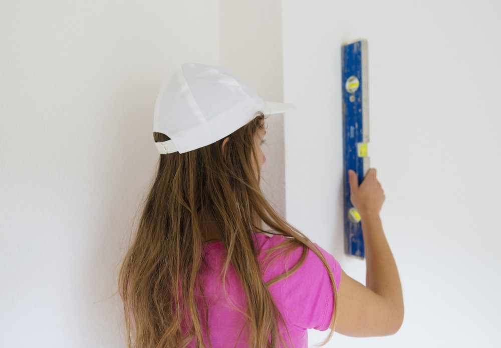 Rear view of young woman measuring the wall with level