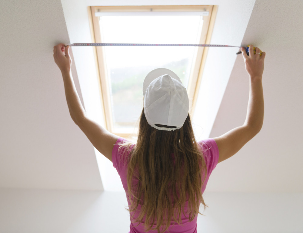 Rear view of young woman measuring the wall with tape measure