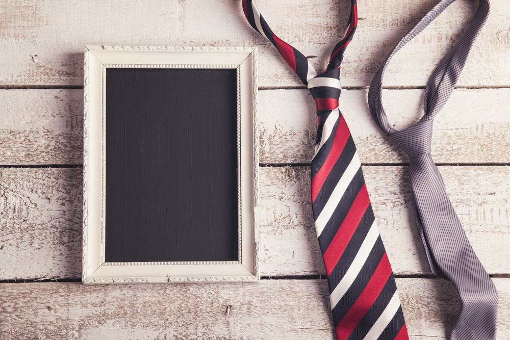 Rectangle picture frame and two ties laid on wooden floor backround.