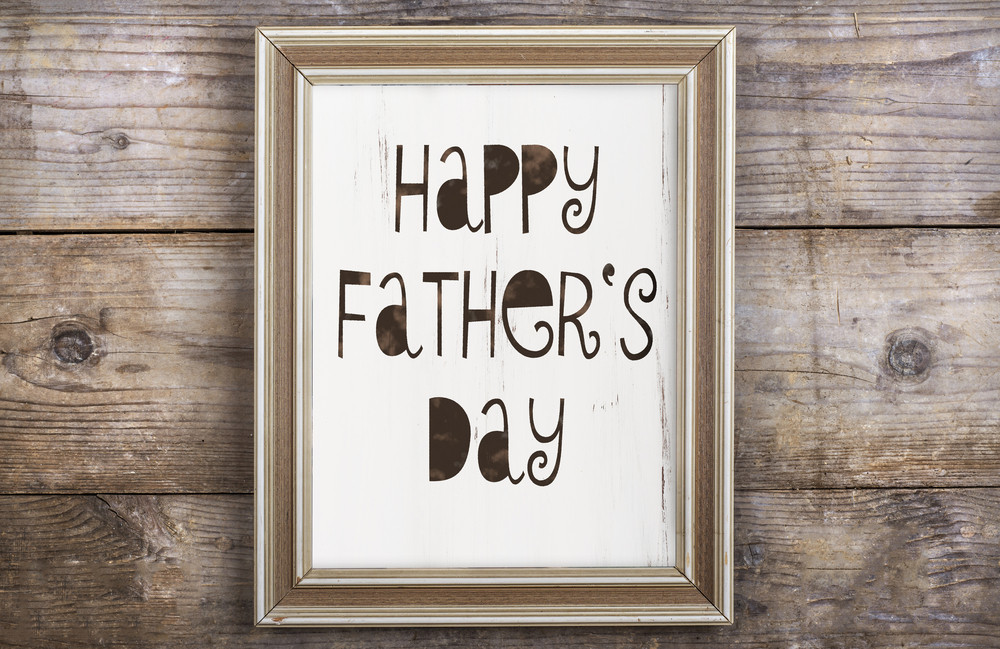 Rectangle picture frame with Happy fathers day sign laid on wooden floor backround.