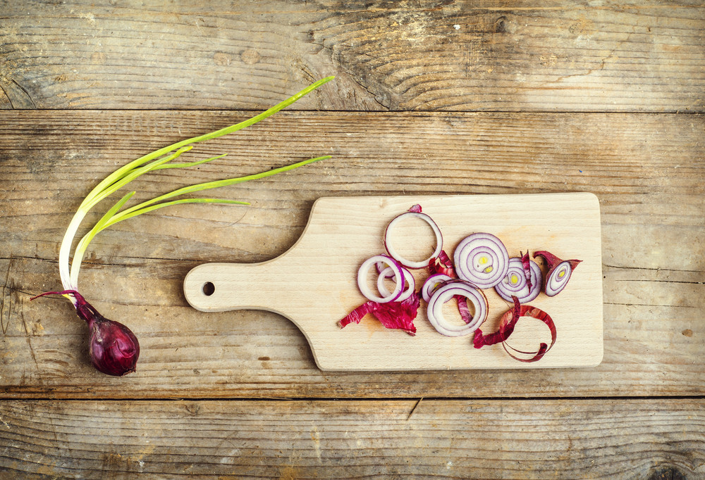 Red onion chopped on a wooden background. View from abowe.