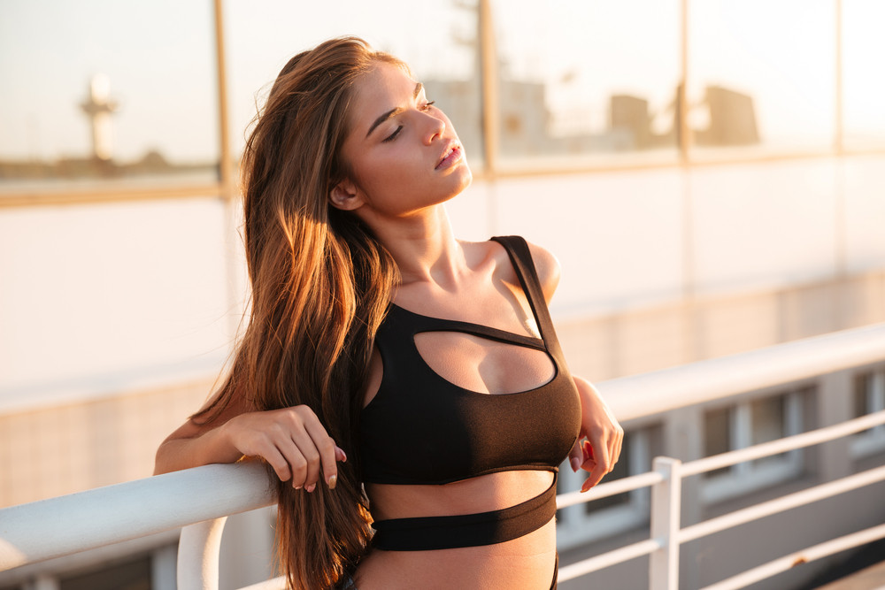 Relaxed lovely young woman in swimsuit standing in the city
