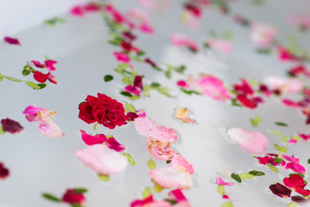 Relaxing herbal bath with beautiful flower petals and leaves.
