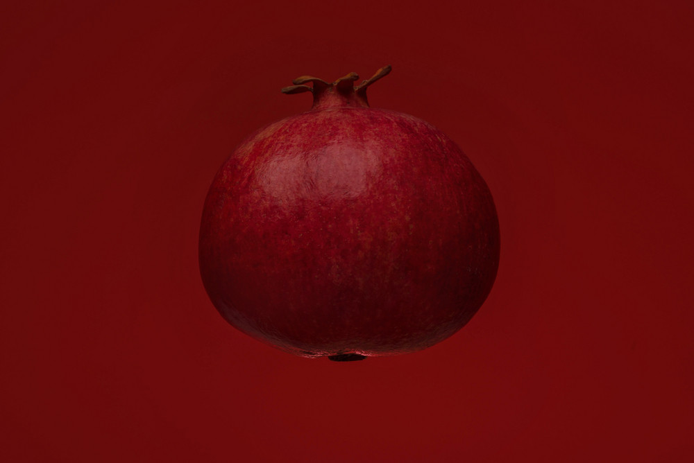 Ripe pomegranate fruit isolated on red background