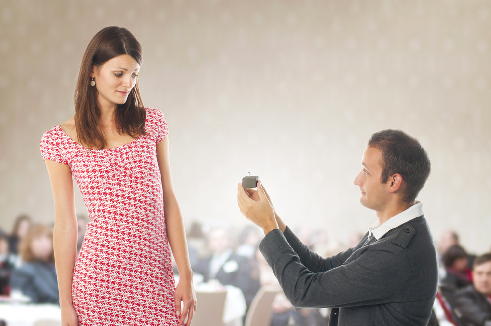 Romantic proposal scene with happy woman and man.