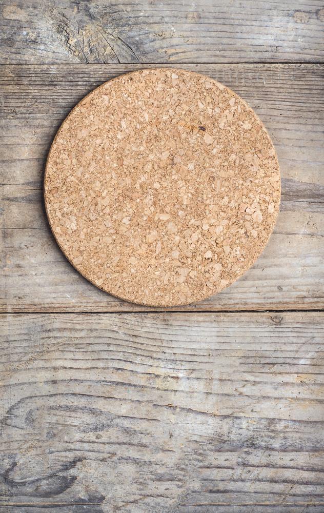 Round cork mat on wooden floor background