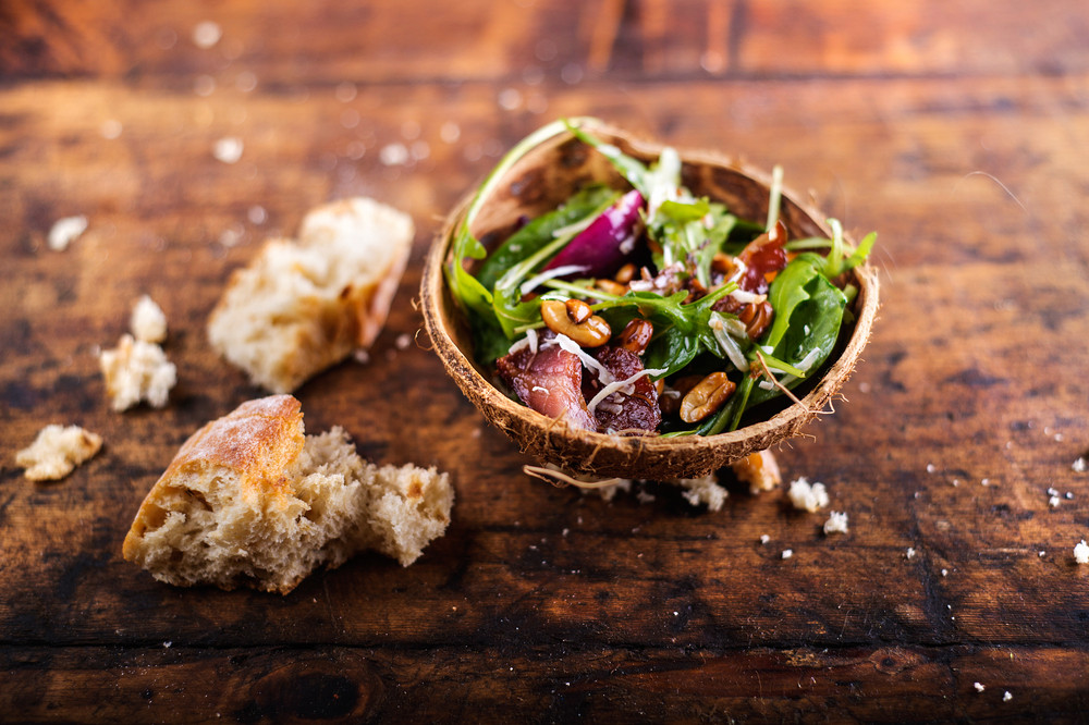 Rucola salad in a bowl made from coconut shell. Studio shot on wooden background.