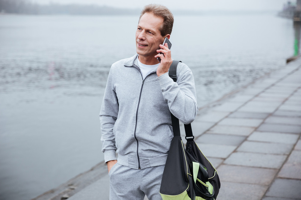 Runner in gray sportswear standing with bag and talking on phone near the river