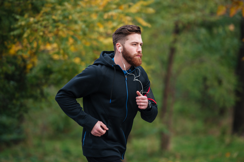 Runner in park. side view. in warm clothes