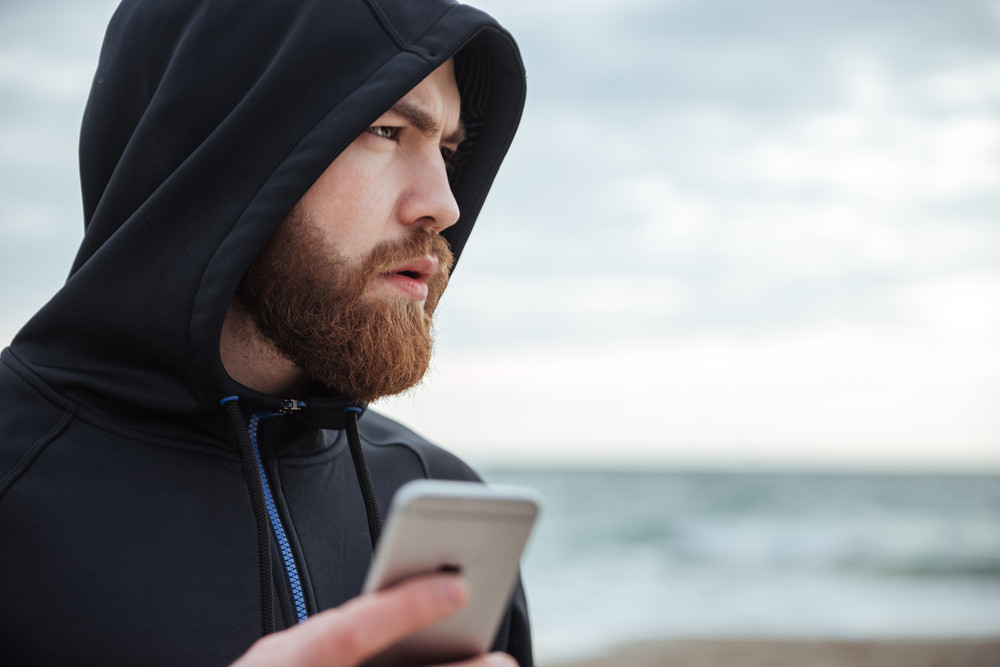 Runner with phone on beach in profile. man in hood