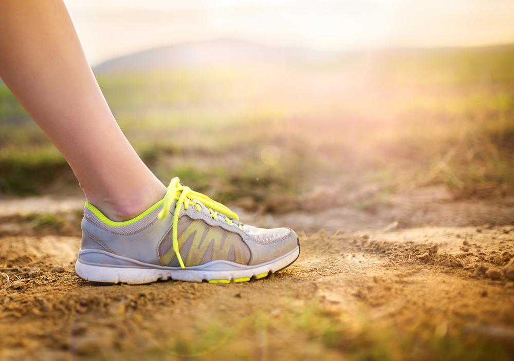 Runner woman feet running on countryside road, closeup on shoe