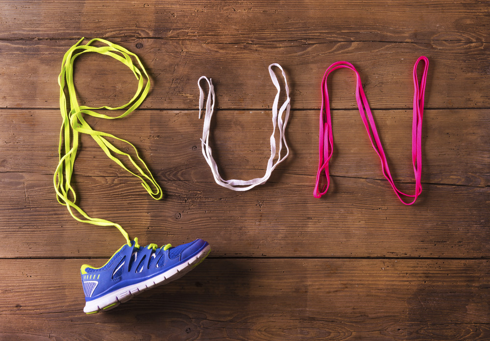 Running shoe and shoelaces run sign on a wooden floor background