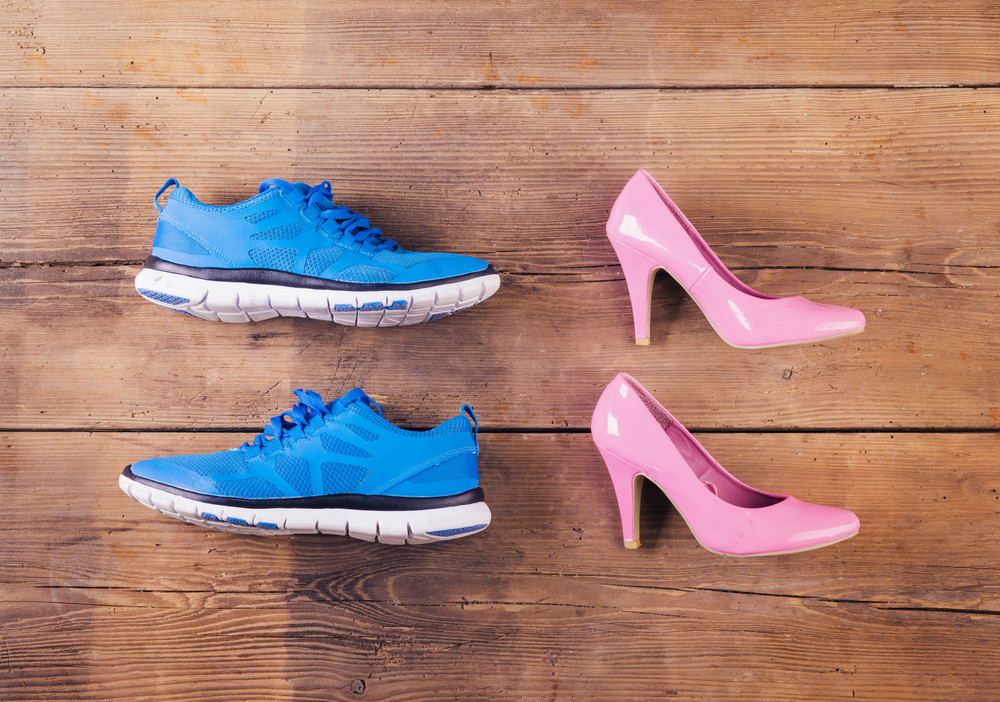 Running shoes and pink court shoes on a wooden floor background