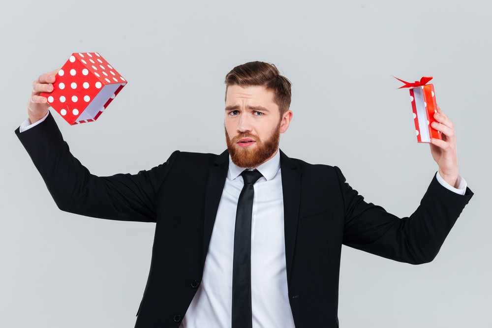 Sad bearded business man in suit with empty open gift looking at camera. Isolated gray background
