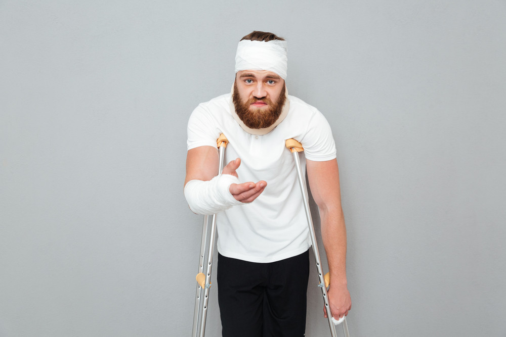 Sad desperate injured man with crutches with outstretched hand over white background