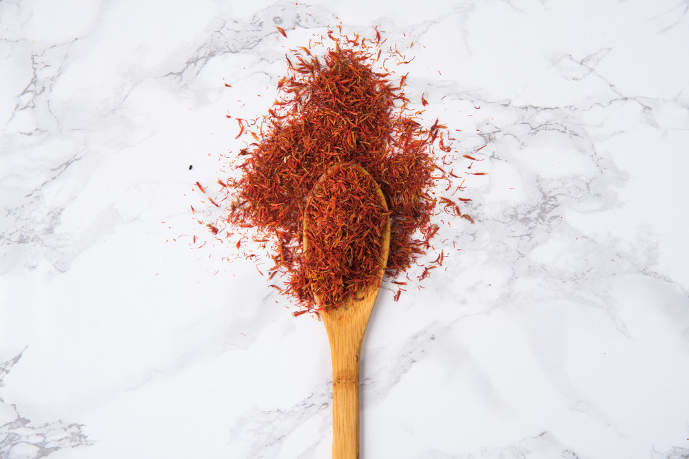 Saffron spice in wooden spoon isolated on white marble background