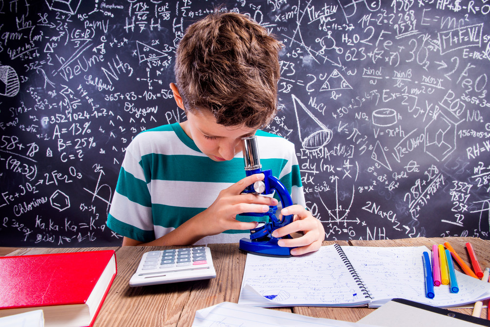 School boy sitting at the desk with microscope and other school supplies against big blackboard with formulas and mathematical symbols