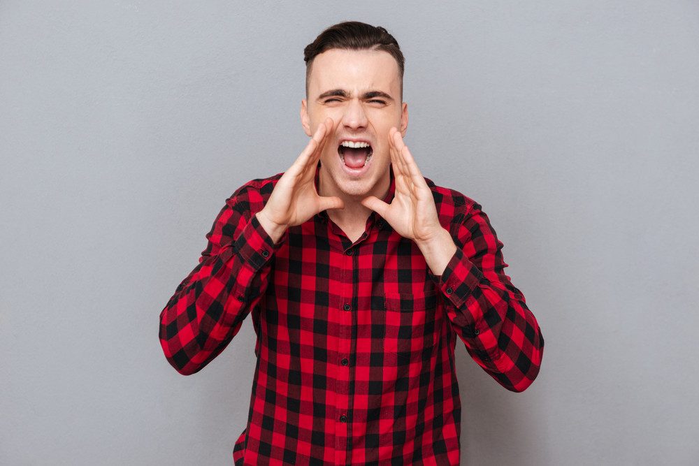 Screaming young man in shirtholding hands near the face and looking at camera. isolated gray background