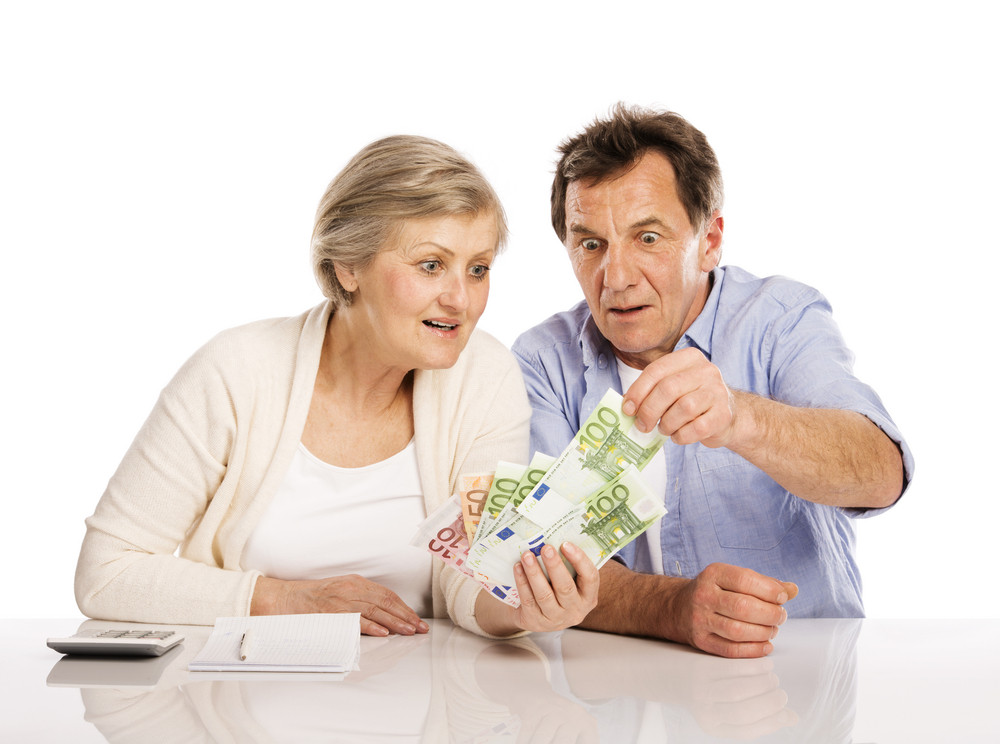 Senior couple counting money at the table, isolated on white background