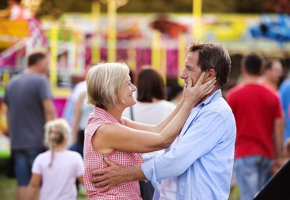 Senior couple having a good time at the fun fair