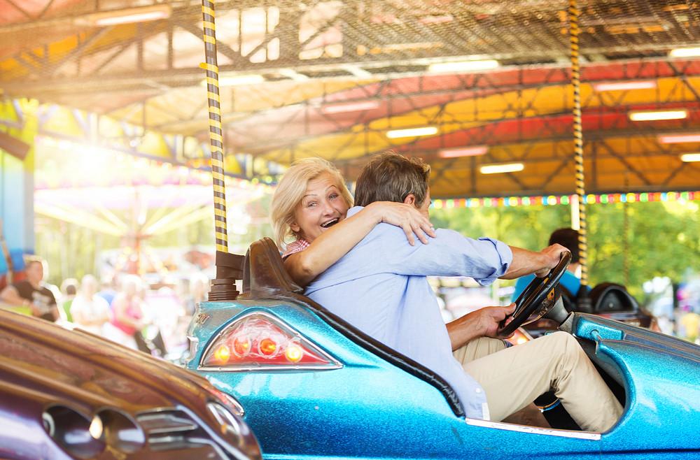 Senior couple having a ride in the bumper car at the fun fair