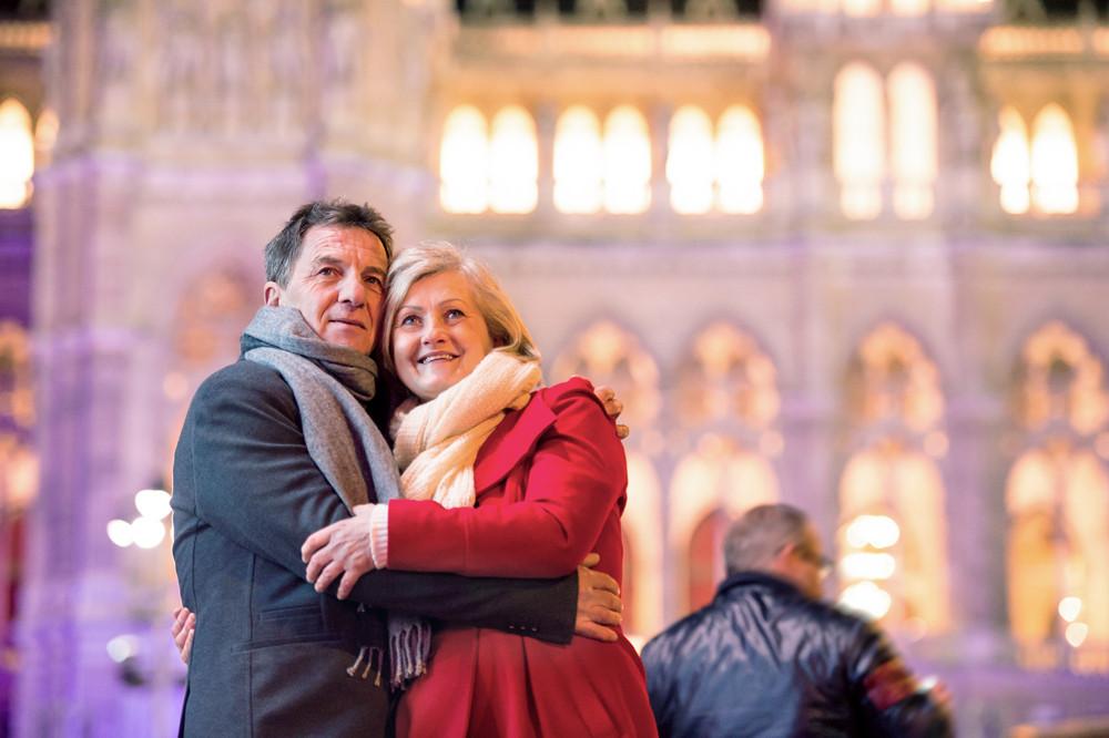 Senior couple in winter clothes on a walk in illuminated night city. Historical building. Vienna, Austria.