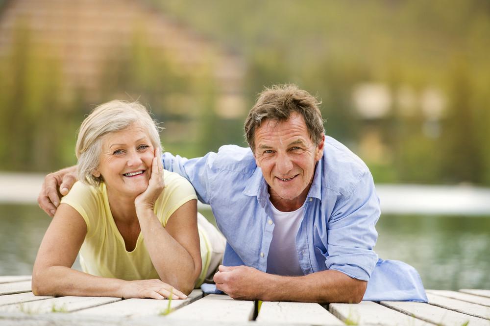 Senior couple lying down and having fun on pier