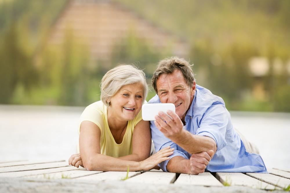 Senior couple lying down and taking selfie on pier