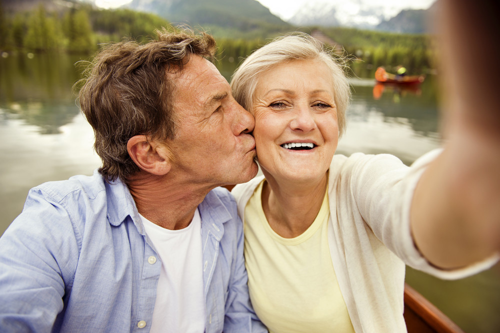 Senior couple on boat with mountains in background taking selfie
