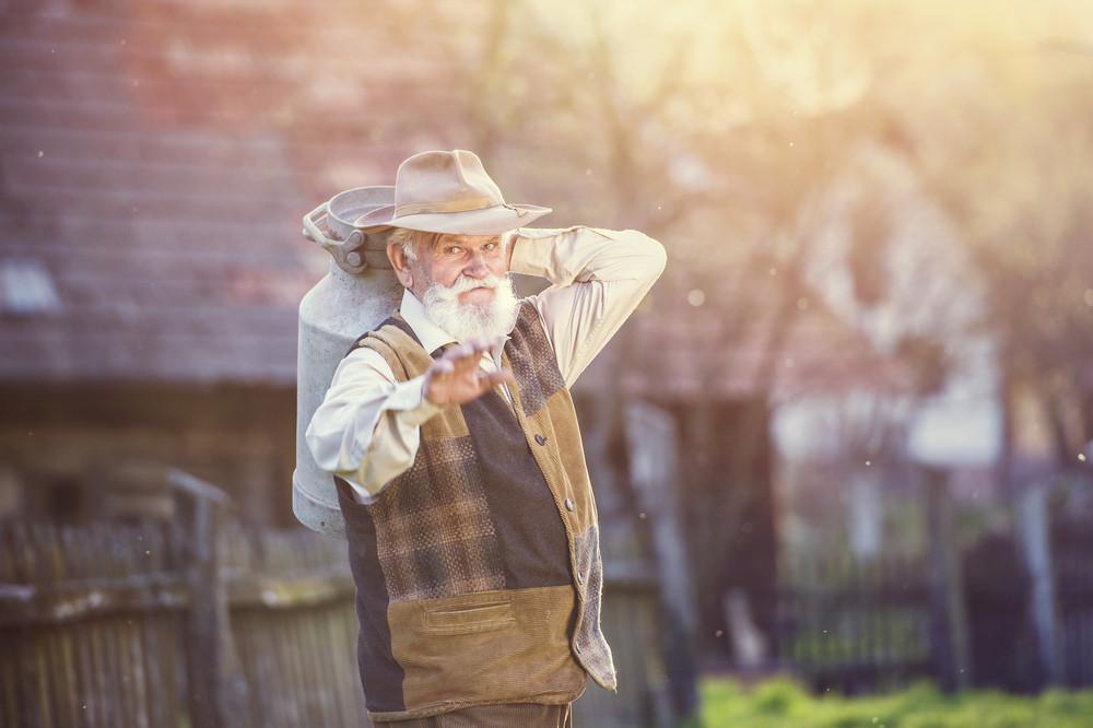 Senior farmer carrying kettle full of milk on his back