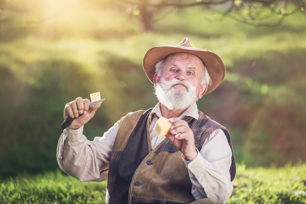Senior farmer cutting and eating cheese outside in green nature