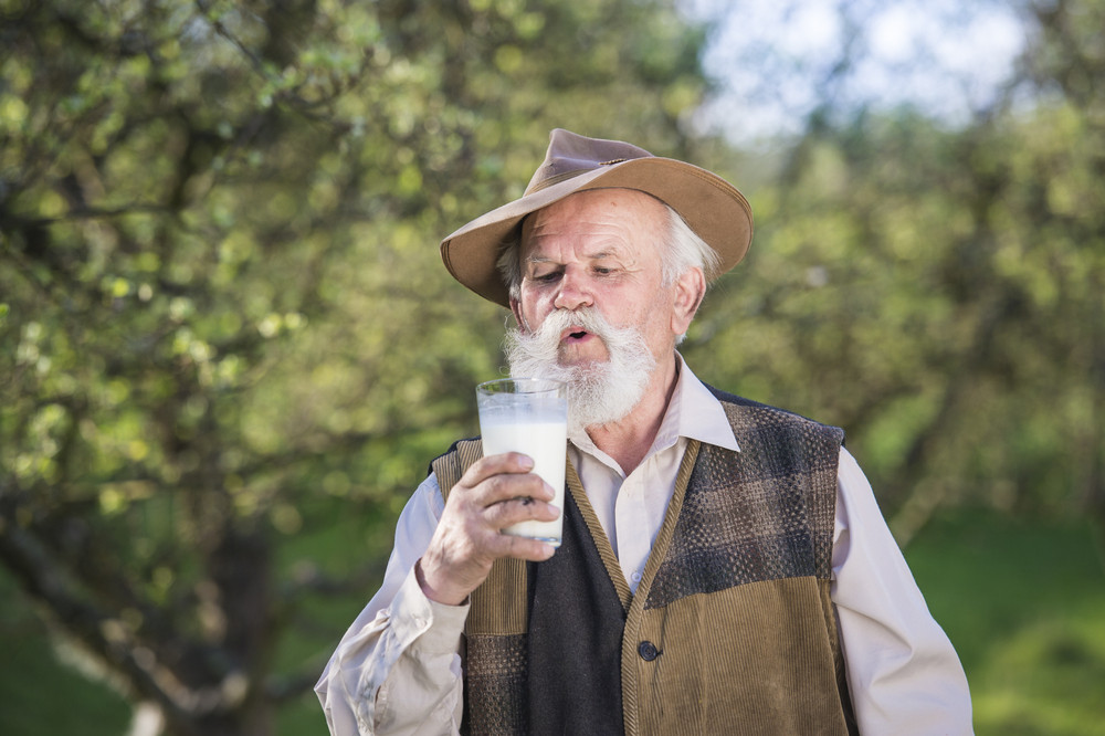 Senior farmer with a glass of milk outside in green nature