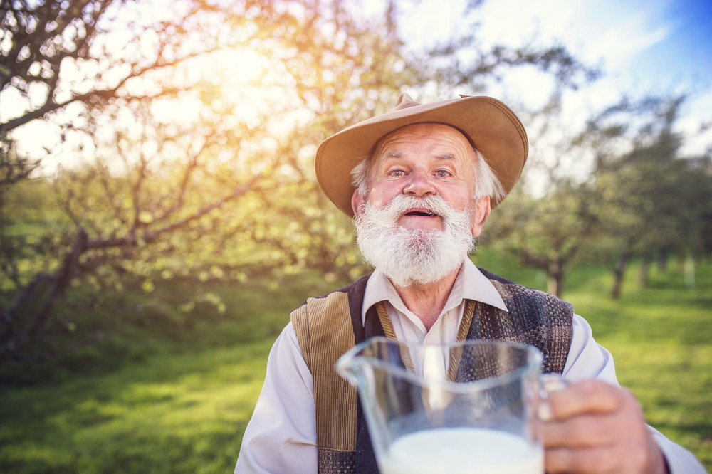 Senior farmer with milk in a glass jug outside in green nature
