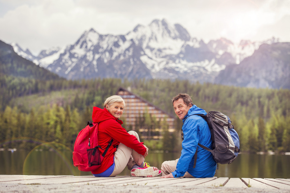 Senior hikers couple during the walk round the tarn in beautiful mountains, hills and hotel in background