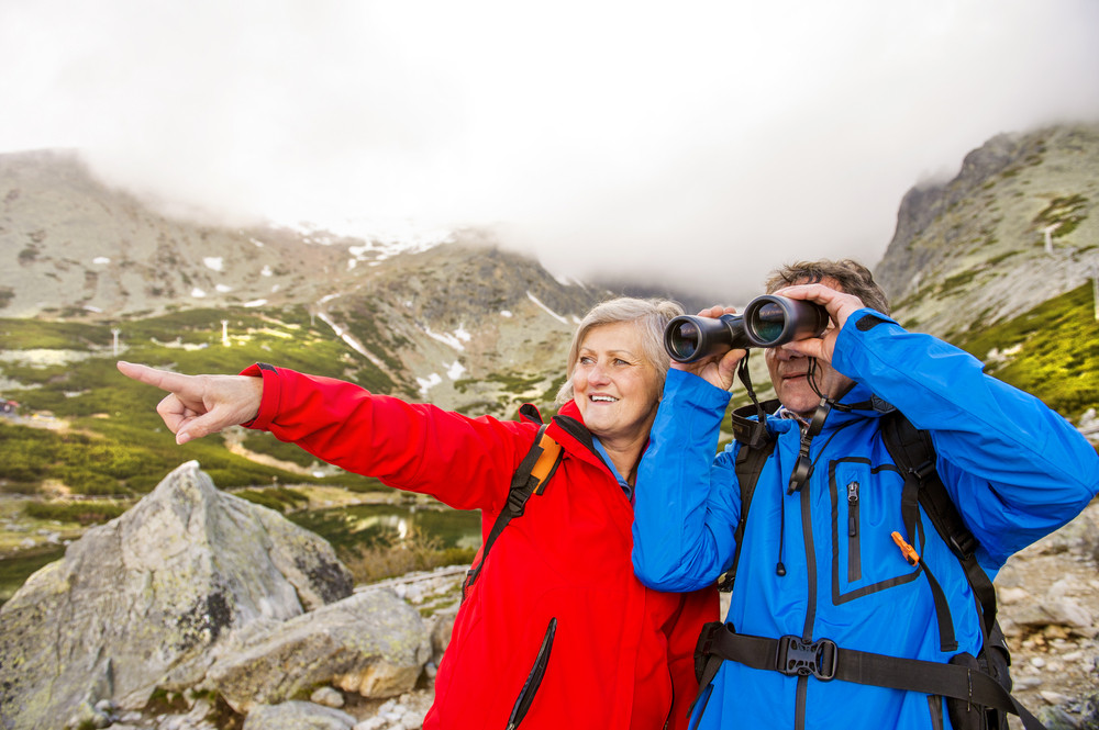 Senior hikers couple enjoying the landscape view with binoculars