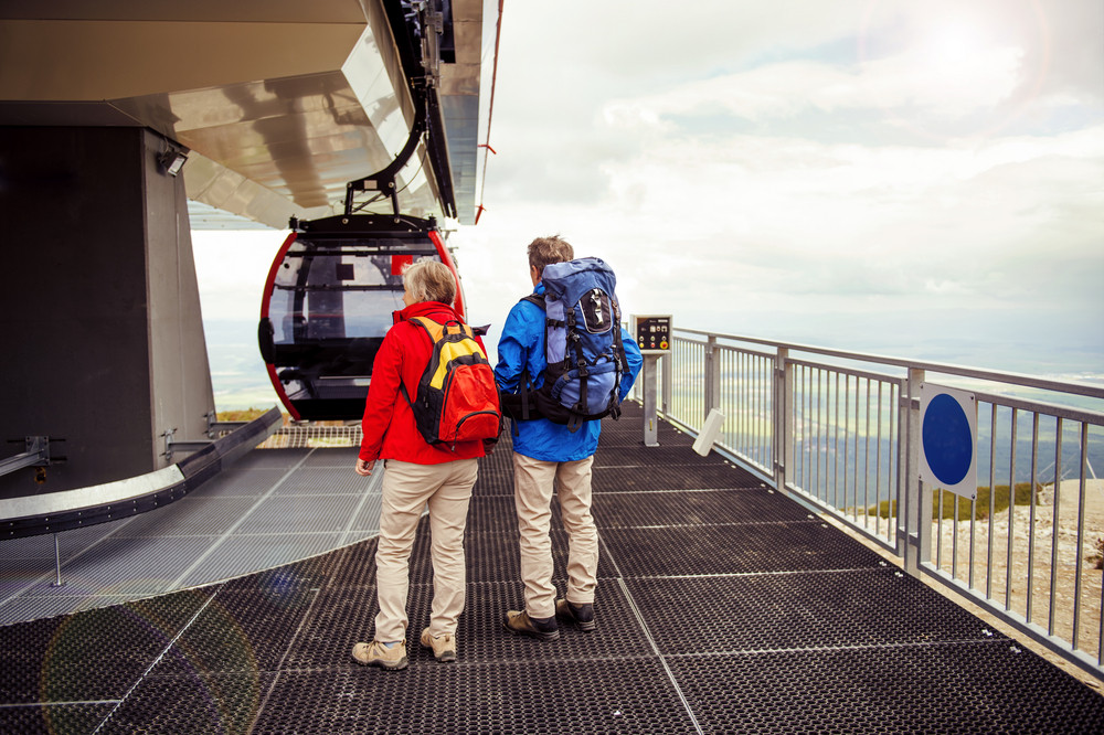 Senior hikers couple is waiting for cableway in cable station