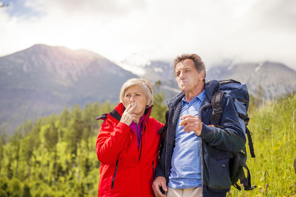 Senior hikers couple smoking during the walk in the mountains