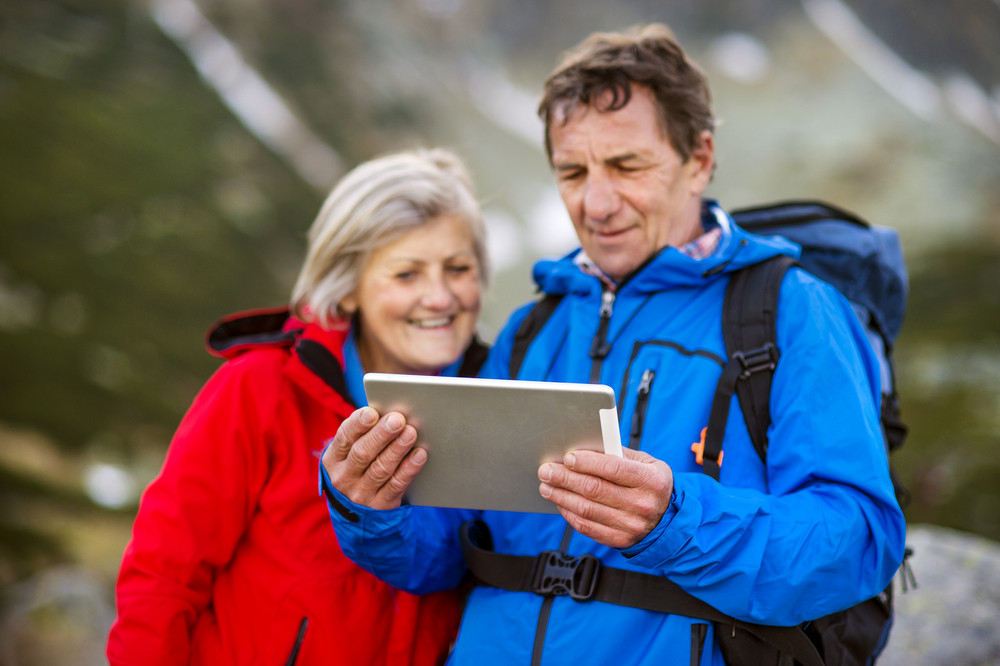 Senior hiking couple using travel app or map on tablet during the hike.