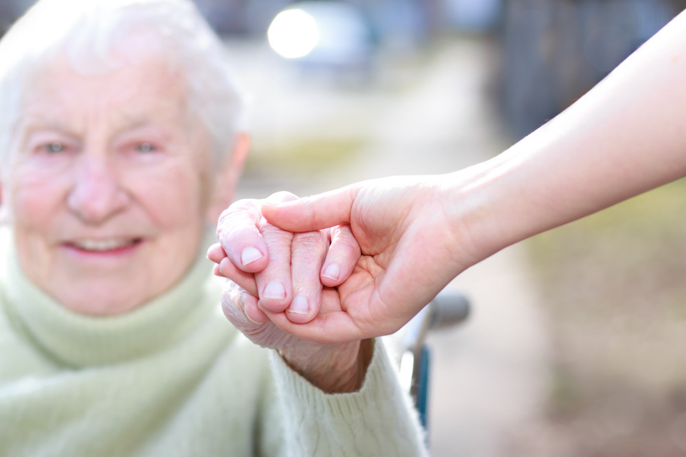 Senior Lady in Wheelchair and Young Woman Holding Hands Outside