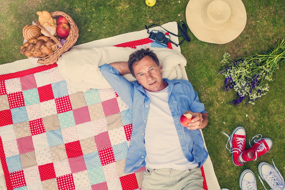 Senior man having a picnic lying on a colorful blanket