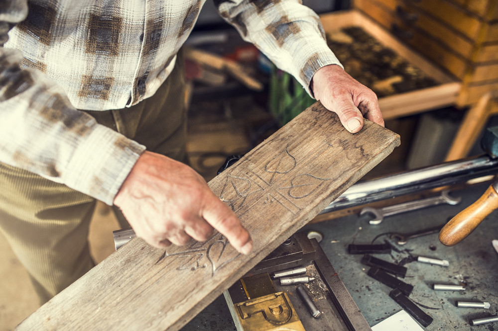 Senior man holding in his hands engraved wooden plank