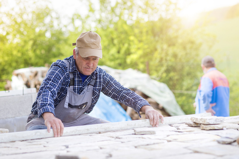 Senior man  in checked shirt laying a stone path
