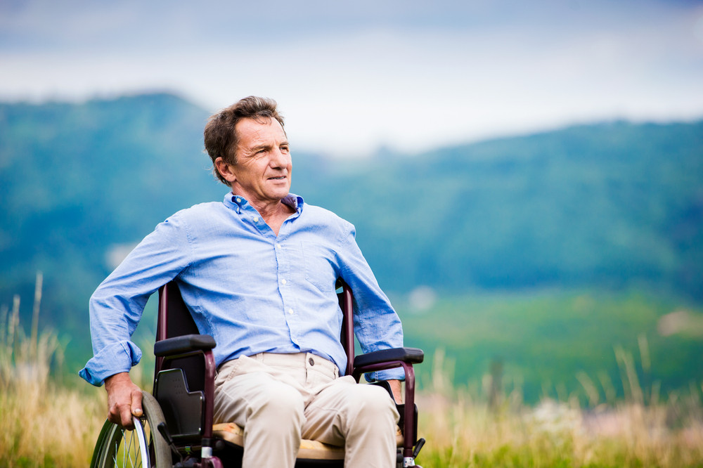 Senior man in wheelchair outside in nature