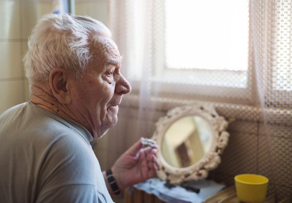 Senior man shaving his beard in bathroom in front of the mirror