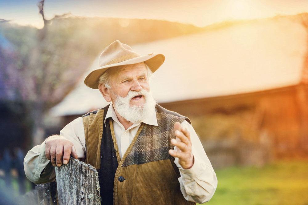 Senior man standing outside at the wooden fence