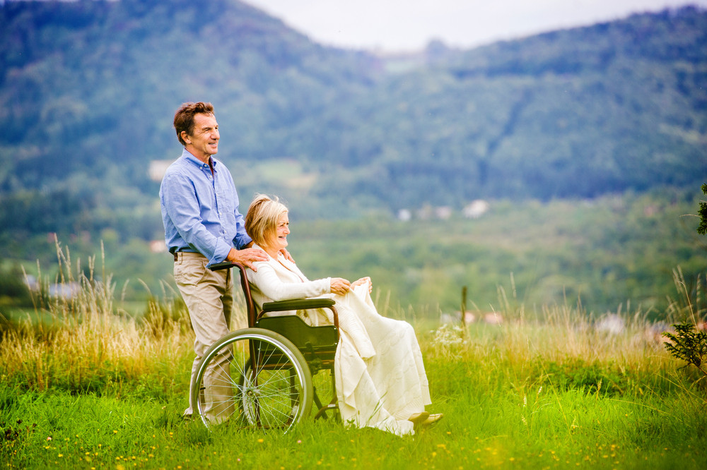 Senior man with woman in wheelchair outside in nature