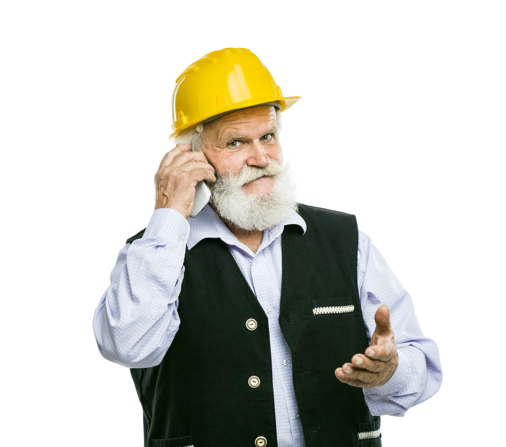 Senior manual worker with yellow helmet calling on the phone isolated over white background