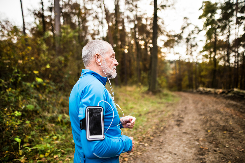 Senior runner in nature. Man with smart phone and earphones. Listening music or using a fitness app. Using phone app for tracking weight loss progress, running goal or summary of his run.