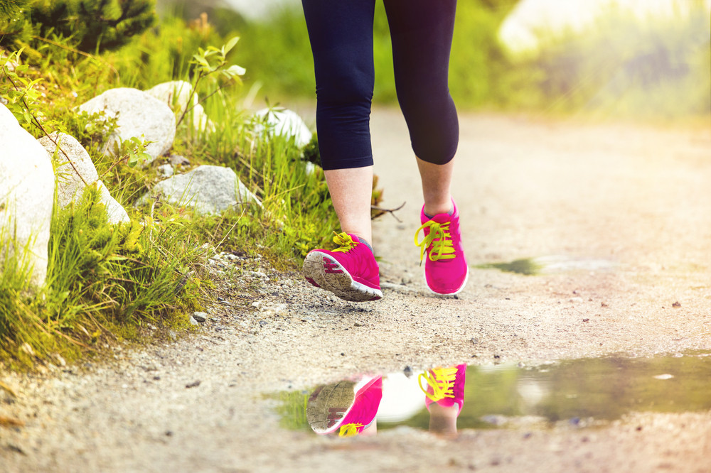 Senior runner woman feet running in beautiful nature reflecting in puddle, closeup on feet